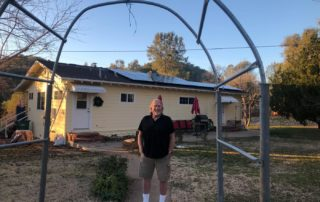 SolarWorx Energy client in front of house with new solar panels in Tuolumne County California